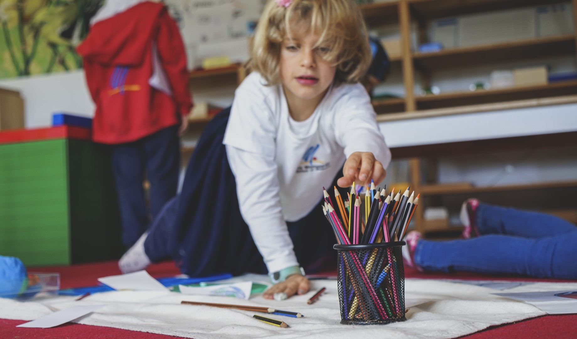 A girl in the primary classroom working on the floor in front of shelves with learning material