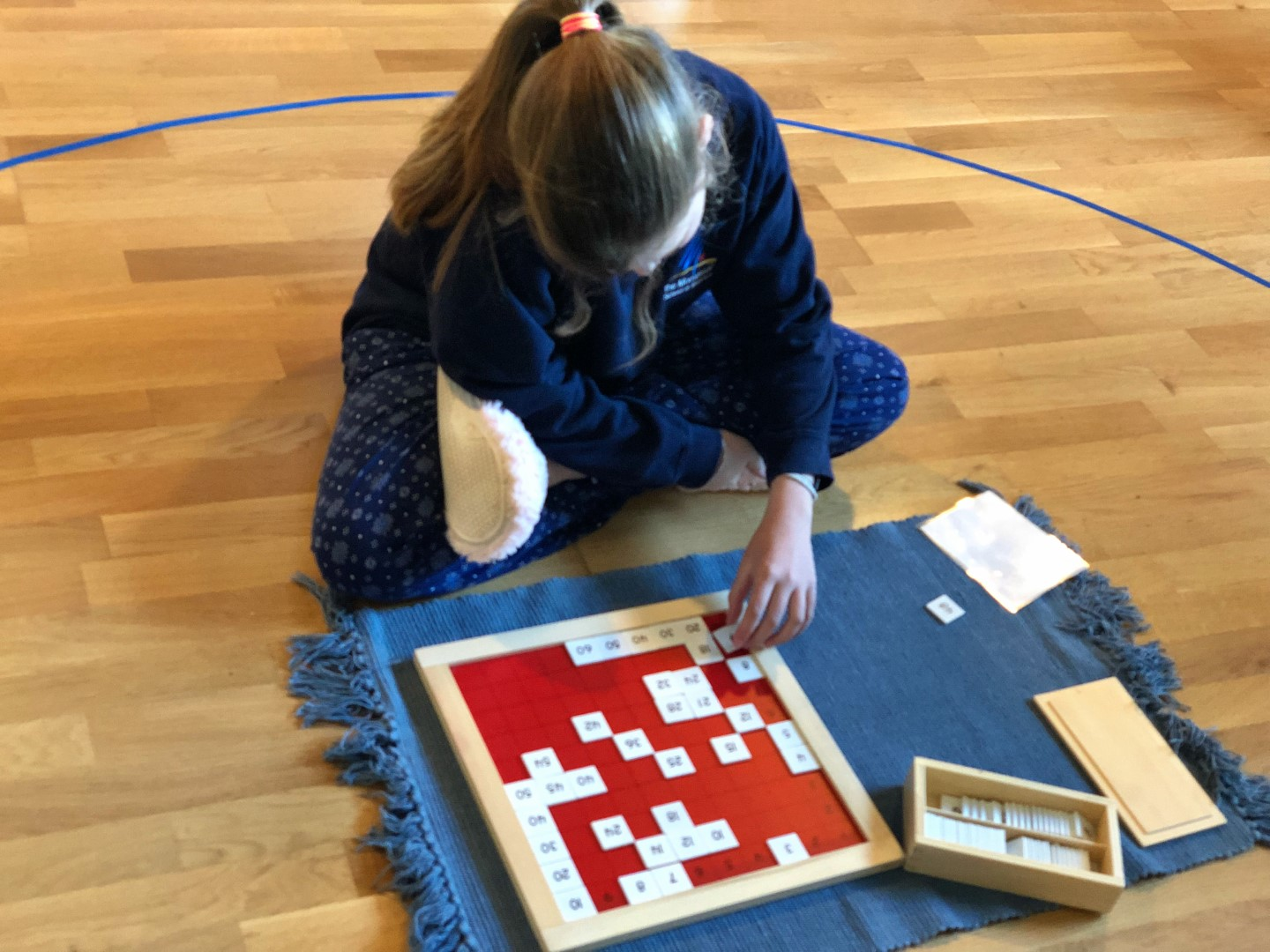 Child on the floor doing work with Montessori materials